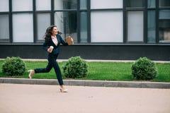 jonge glimlachende onderneemster die aan het werk met koffie lopen stock foto's