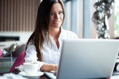 Jonge glimlachende onderneemster op een onderbreking in een koffie Zij werkt bij laptop en het drinken koffie royalty-vrije stock afbeelding