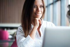 Jonge glimlachende onderneemster op een onderbreking in een koffie Zij werkt bij laptop en het drinken koffie stock foto's