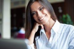 Jonge glimlachende onderneemster op een onderbreking in een koffie Zij werkt bij laptop en het drinken koffie royalty-vrije stock foto