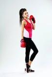 Jonge glimlachende sportenvrouw die zich met bokshandschoenen bevinden Stock Foto