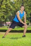 Jonge glimlachende sportman die in een park uitoefenen Stock Foto's