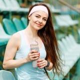 Jonge glimlachende sportvrouw met fles water stock foto