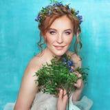 Jonge glimlachende tedere vrouw met blauwe bloemen op lichtblauwe achtergrond Het Portret van de de lenteschoonheid Royalty-vrije Stock Foto