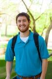 Jonge, glimlachende universiteits mannelijke student buiten Stock Foto