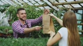 Jonge glimlachende verkopersbloemist die in tuincentrum werken De mens geeft het winkelen zak aan klant en het verrichten van bet Royalty-vrije Stock Afbeeldingen