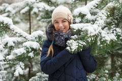 Jonge glimlachende vrouw die de blauwe echte benedenlaag dragen die met een kap van de bontversiering van mening in de winterbos  Royalty-vrije Stock Foto's