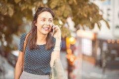 Jonge, glimlachende vrouw die een celtelefoon uitnodigen stock fotografie