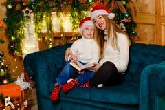 Jonge glimlachende vrouw die een kindzitting op de laag koesteren bij Kerstmis stock afbeelding