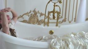 Jonge glimlachende vrouw die in het bad in uitstekende badkamers, dicht liggen omhoog gekleed in baltoga stock footage
