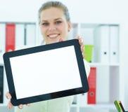 Jonge glimlachende vrouw die het lege scherm van de tabletcomputer in bureau tonen Royalty-vrije Stock Fotografie