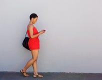 Jonge glimlachende vrouw die met mobiele telefoon en oortelefoons lopen stock afbeeldingen