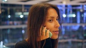 Jonge Glimlachende Vrouw die op Mobiele Telefoon in Winkelcomplex spreken Aantrekkelijk Gemengd Rasmeisje die Smartphone met Vaag stock video