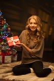 Jonge glimlachende vrouw die rode Kerstmisgift houdt stock foto