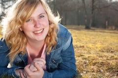 Jonge glimlachende vrouw in het gras stock afbeeldingen