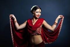 Jonge glimlachende vrouw in het traditionele Indische kleding dansen Royalty-vrije Stock Foto's