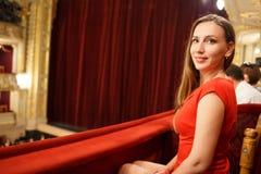 Jonge glimlachende vrouw in kledingszitting in theater stock afbeelding