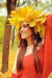 Jonge glimlachende vrouw met kroon van esdoornbladeren op een hoofd, openluchtportret royalty-vrije stock afbeelding