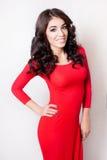 Jonge glimlachende vrouw met lange krullende bruine haar rode kleding Stock Foto's