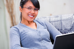 Jonge glimlachende vrouw met laptop thuis Stock Foto