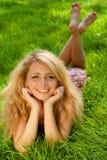 Jonge glimlachende vrouw op het gras royalty-vrije stock foto