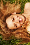 Jonge glimlachende vrouw op het gras stock afbeeldingen