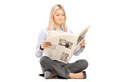 Jonge glimlachende vrouw sittng op een vloer en het lezen van een krant stock afbeelding