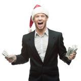 Jonge glimlachende zakenman in de holdingsgeld van de santahoed Stock Afbeeldingen