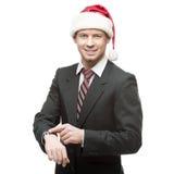 Jonge glimlachende zakenman die in santahoed op horloge richten Royalty-vrije Stock Afbeelding
