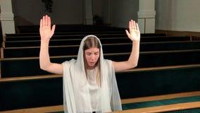 Jonge godsdienstige toegewijde vrouw die in doopsgezinde kerk bidden Gelovige katholiek bij Europese kathedraal: binnen van heili stock footage