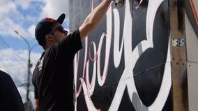 Jonge graffitikunstenaar die in de straat werken stock videobeelden