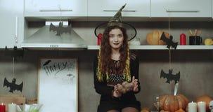 Jonge grappige die dame in een heks bij Halloween-nacht het spelen met een aardappel voor de zeer charismatische camera wordt gem stock videobeelden