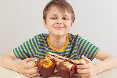 Jonge grappige jongen in een gestreept overhemd bij de lijst met muffins en sandwich op witte achtergrond stock foto