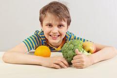 Jonge grappige jongen in een gestreept overhemd bij de lijst met vruchten en groenten op witte achtergrond stock foto's