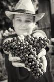 Jonge grappige jongen met zwart-witte bos van druiven in handen, royalty-vrije stock foto's