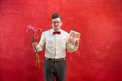 Jonge grappige mens met bloemen en gift Stock Afbeelding