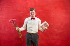 Jonge grappige mens met bloemen en gift Royalty-vrije Stock Afbeelding
