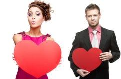 Jonge grappige vrouw en knappe man die rood hart op witte bedelaars houden Royalty-vrije Stock Fotografie