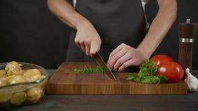 Jonge greens van het chef-kokknipsel in de geïsoleerde donkere keuken stock footage