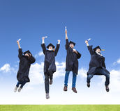 jonge groep graduatiestudenten die samen springen Stock Afbeeldingen