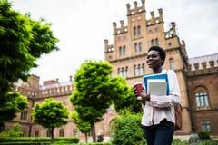 Jonge groep studenten met rugzakken en boeken met Campus als achtergrond Afro Amerikaans meisje met notitieboekjes en kop van kof stock afbeeldingen