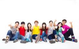 Jonge groepszitting samen met duim omhoog Stock Foto's