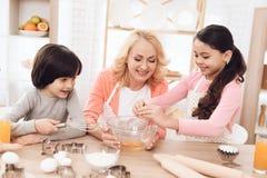 Jonge grootmoeder en kleinkinderenonderbrekingseieren in kom in keuken Het Llittlemeisje leert te koken stock afbeeldingen