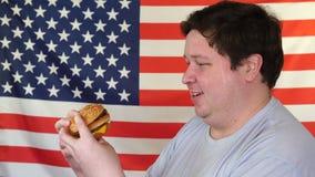 Jonge grote mens die met vet gezicht etend hamburgers genieten die op Amerikaanse vlagachtergrond wordt geïsoleerd stock video