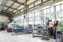 Jonge handarbeiders werkende machines in de metaalindustrie stock fotografie