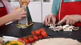 Jonge handen die pizza in de keuken thuis maken stock video