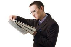 Jonge hansome mens in kostuum gelezen krant Stock Fotografie