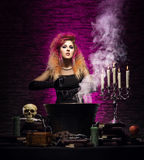 Jonge heks die hekserij in een Hallowen-kerker maken royalty-vrije stock afbeelding