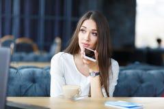 Jonge het bedrijfsvrouw drinken koffie in het restaurant Laptop en smartphone op de lijst stock fotografie