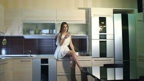 Jonge het glimlachen meisjeszitting op countertop in de keuken met in hand telefoon stock footage